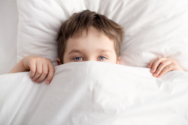 little boy covering nose with bed sheet